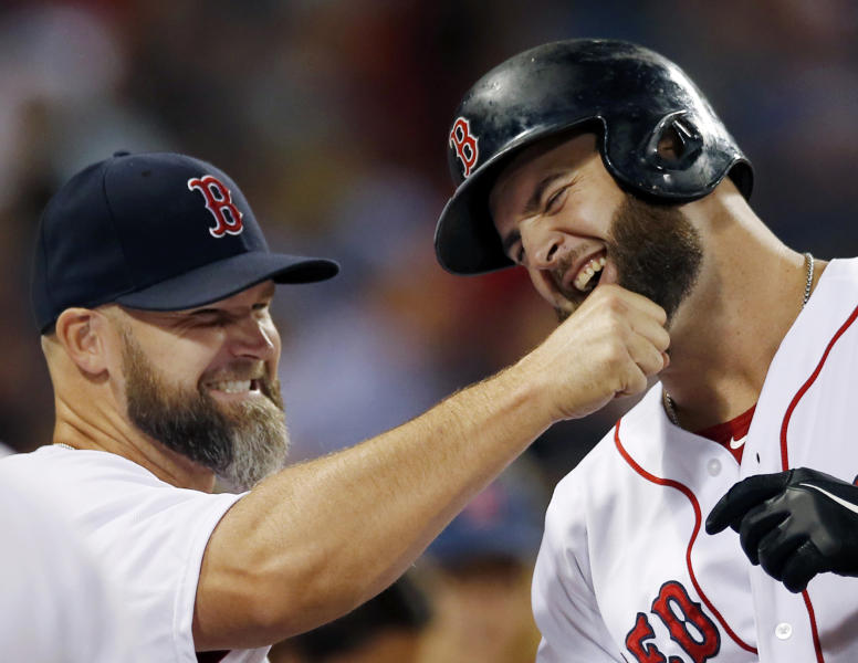 Boston Red Sox's Mike Napoli, right, has his beard tugged by teammate David Ross at the dugout in celebration of Napoli's solo home run against the Baltimore Orioles in the fourth inning of a baseball game at Fenway Park in Boston, Tuesday, Aug. 27, 2013. (AP Photo/Elise Amendola)