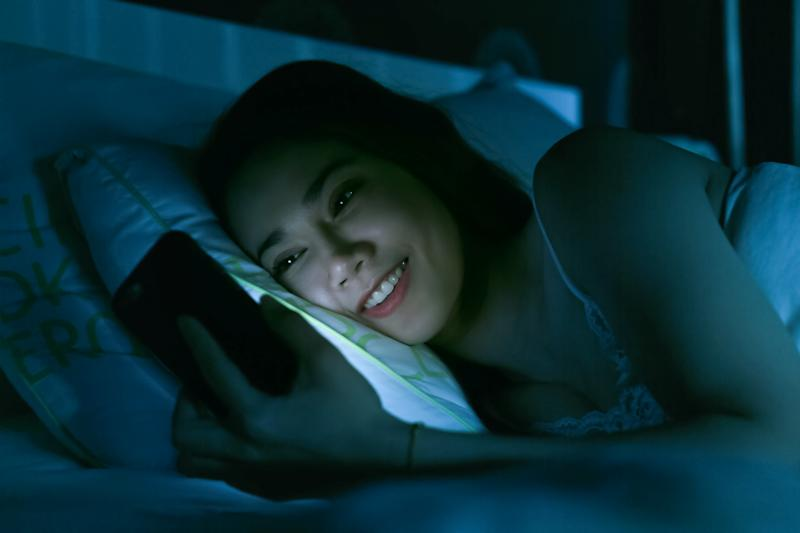 Smiling Woman Using Mobile Phone While Lying On Bed At Night