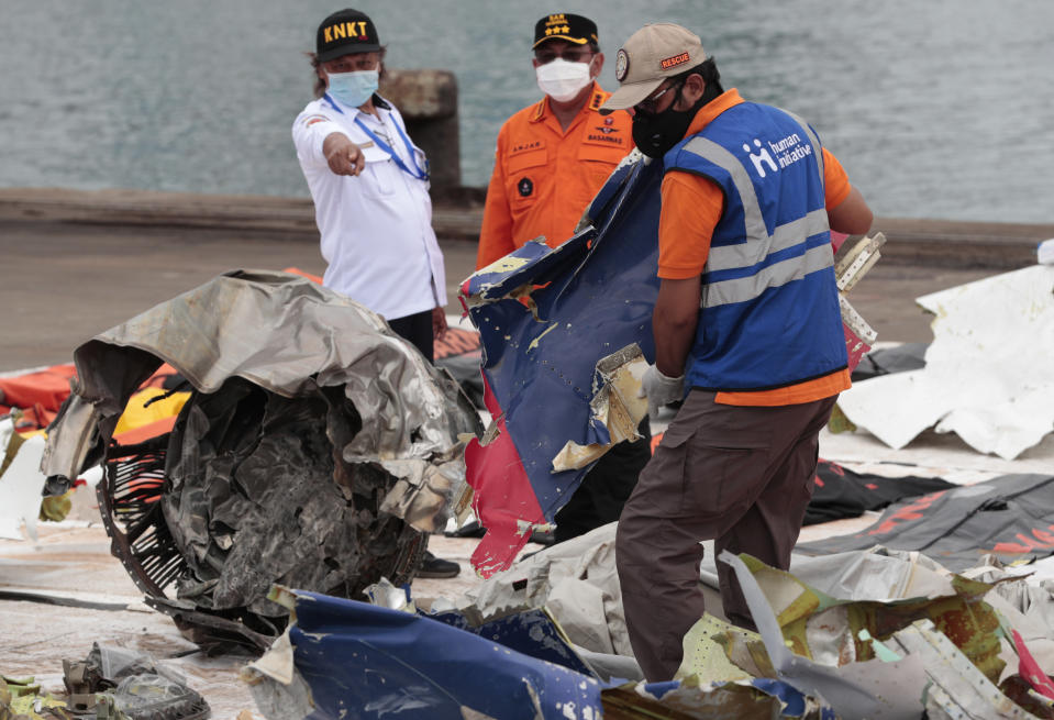 A worker carries parts of aircraft and debris retrieved from from the Java Sea where a Sriwijaya Air jet crashed on Saturday, at Tanjung Priok Port in Jakarta, Indonesia, Thursday, Jan. 14, 2021. An aerial search for victims and wreckage of a crashed Indonesian plane expanded Thursday as divers continued combing the debris-littered seabed looking for the cockpit voice recorder from the lost Sriwijaya Air jet. (AP Photo/Dita Alangkara)