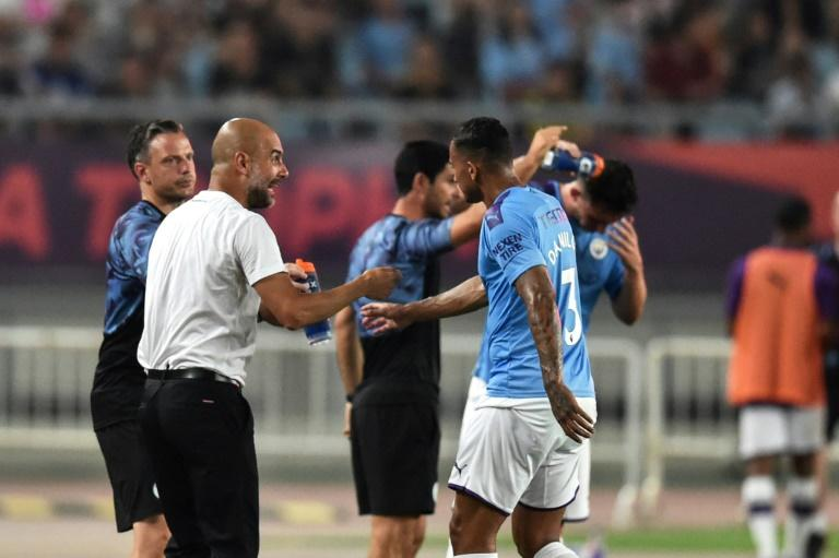 Pep Guardiola gives intructions to his Manchester City players on the sideline in Nanjing