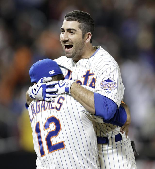 New York Mets Josh Satin leaps into the arms of teammate Juan Lagares after hitting a ninth-inning walkoff two-run single to lift the Mets to a 5-4 victory over the San Francisco Giants in a baseball game on Wednesday, Sept. 18, 2013, in New York. (AP Photo/Kathy Willens)