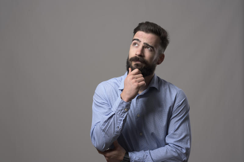 Young adult hipster business man thinking and looking up at copyspace while touching beard against gray studio background.