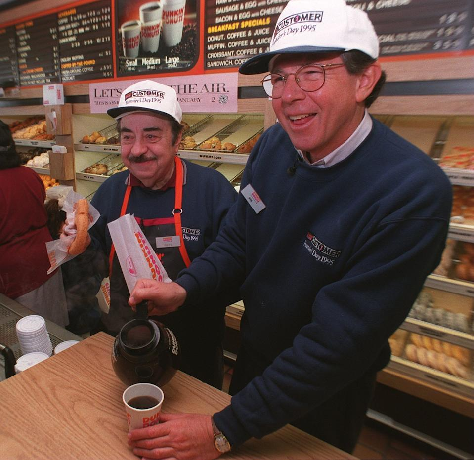 """QUINCY, MA - JANUARY 31: Dunkin' Donuts CEO Bob Rosenberg pours a customer coffee as actor Michael Vale who plays """"Fred the Baker"""" in TV commercials gets ready with a donut at the original Dunkin' Donuts location in Quincy, MA on Jan. 31, 1995. Rosenberg used to work at this store in 1959. (Photo by David L. Ryan/The Boston Globe via Getty Images)"""