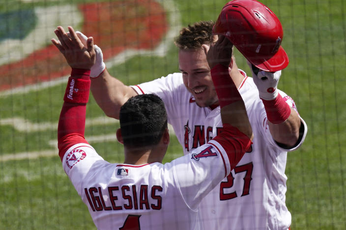 Los Angeles Angels' Mike Trout, right, is congratulated by Jose Iglesias after hitting a two-run home run during the first inning of a baseball game against the Houston Astros Tuesday, April 6, 2021, in Anaheim, Calif. (AP Photo/Mark J. Terrill)