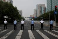 Police and security personnel block a road before a rehearsal of a fireworks display near the National Stadium ahead of the 100th founding anniversary of the Communist Party of China in Beijing