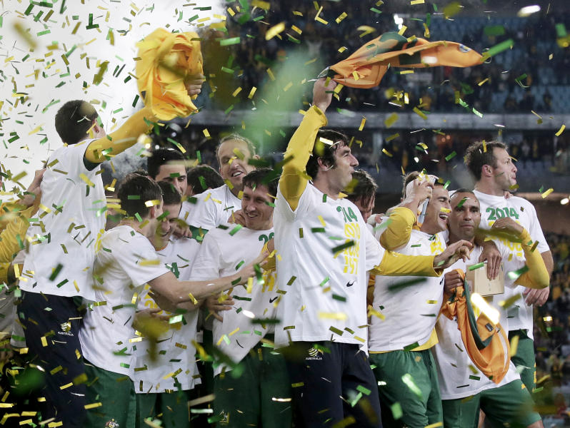 Australia's teammates celebrate their victory over Iraq in their World Cup soccer Asian qualifying match at the Sydney Olympic Stadium in Sydney, Australia, Tuesday, June 18, 2013. Australia won the match 1-0 and qualify for the 2014 World Cup in Brazil. (AP Photo/Rick Rycroft)