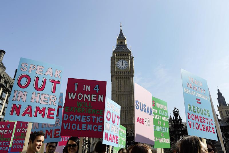 FILE - In this Tuesday, March 5, 2013 file photo people hold banners during a demonstration against domestic violence near Big Ben in London, in the lead up to International Women's Day. About a third of women worldwide have been physically or sexually assaulted by a former or current partner, according to the first major review of violence against women. In a series of papers released on Thursday June 20, 2013 by the World Health Organization and others, experts estimated nearly 40 percent of women killed worldwide were slain by an intimate partner and that being assaulted by a partner was the most common kind of violence experienced by women. (AP Photo/Kirsty Wigglesworth, File)