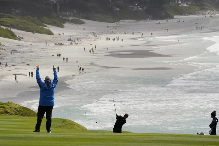 Luke Donald, center, hits from the ninth fairway of the Pebble Beach Golf Links during the second round of the AT&T Pebble Beach Pro-Am golf tournament Friday, Feb. 12, 2021, in Pebble Beach, Calif. (AP Photo/Eric Risberg)