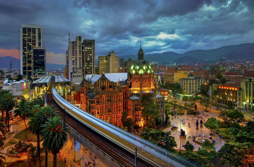 The elevated Medellin Metro is in motion as it rushes into the Parque Berrio Station in front of the illuminated Palace of Culture in Plaza Botero in Medellin, Colombia.  The City of Eternal Spring is located in the Aburra Valley, a central region of the Andes Mountains in South America.
