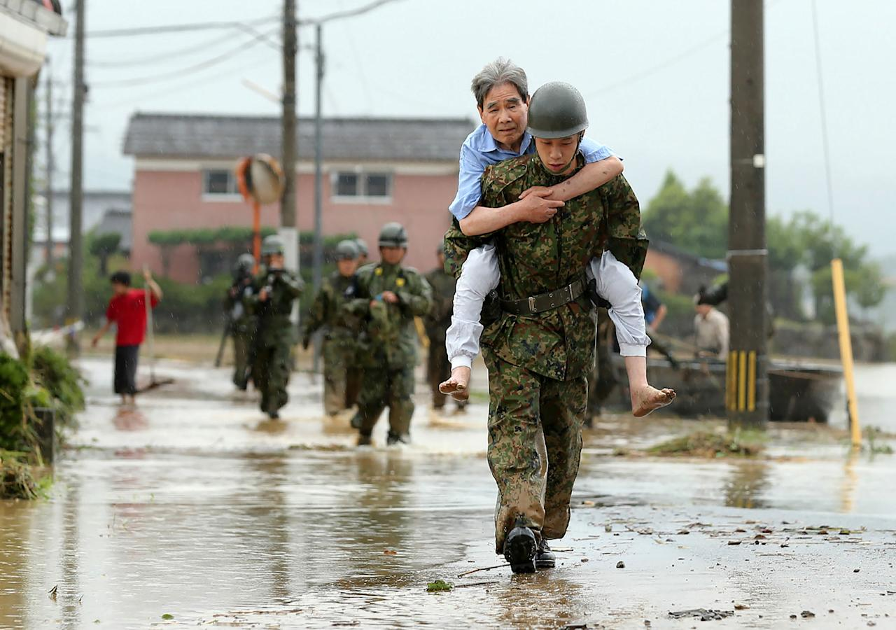 <p>Japanese soldiers help local residents evacuate from flooded area in Asakura, Fukuoka prefecture, on July 6, 2017. More than a dozen people are missing after huge floods swept away houses in southern Japan, tearing up roads as roiling waters surged through villages, authorities said, after unprecedented rainfall.(Photo: STR/AFP/Getty Images) </p>