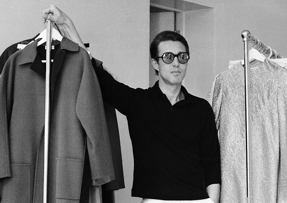 FILE - Women's clothing designer Halston poses among his designs at his showroom in New York on June 25, 1975. A new series about the fashion designer,
