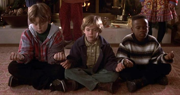Three kids sit cross-legged on the floor, meditating at a party