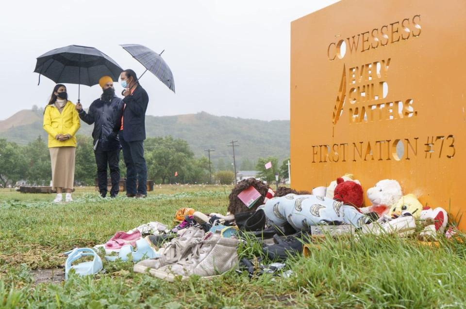 Three people stand holding umbrellas in the background, a sign in the front in orange reads 'ever child matters' teddy bears and other memorabilia lay on the ground in front of it