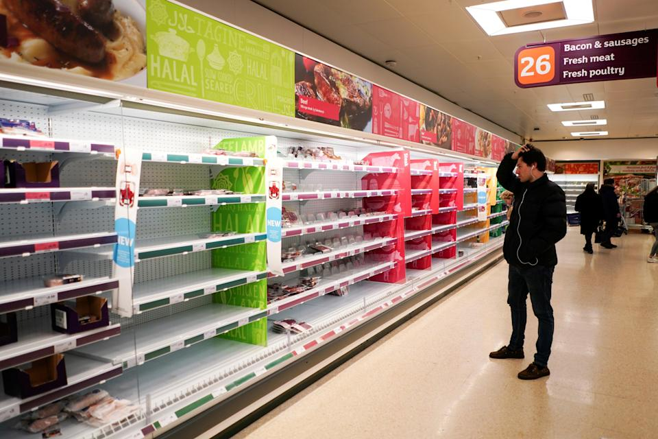 A man stands next to shelves empty of fresh meat in a supermarket in London (REUTERS)