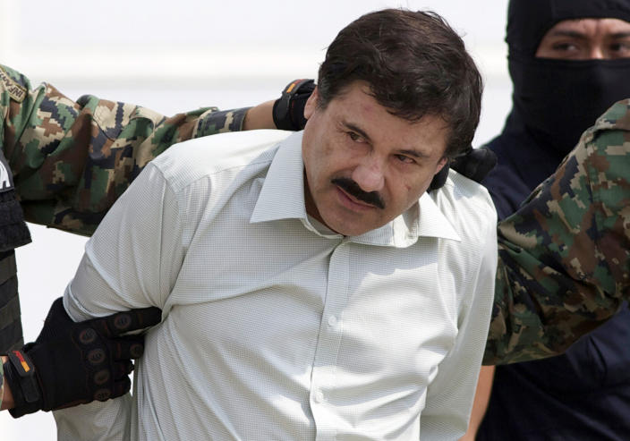 """FILE - In this Feb. 22, 2014 file photo, Joaquin """"El Chapo"""" Guzman, the head of Mexico's Sinaloa Cartel, is escorted to a helicopter in Mexico City following his capture in the beach resort town of Mazatlan, Mexico. The Mexican drug kingpin, who was convicted in a New York federal court in February 2019 on multiple conspiracy counts in an epic drug-trafficking case, was sentenced to life behind bars in a U.S. prison. (AP Photo/Eduardo Verdugo, File)"""