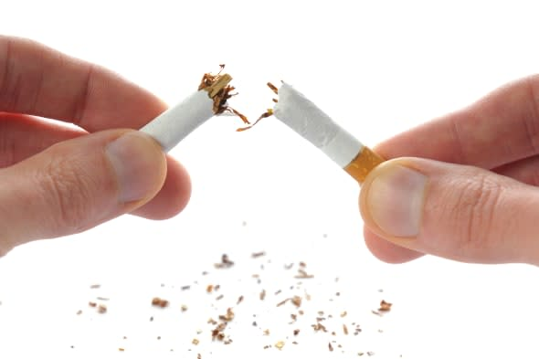 'Quit smoking, cigarette in hands broken in half, isolated on white.'