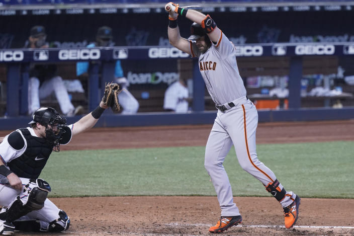 San Francisco Giants' Evan Longoria turns to avoid getting hit by a pitch as Miami Marlins catcher Chad Wallach is unable to catch the ball during the sixth inning of a baseball game, Sunday, April 18, 2021, in Miami. (AP Photo/Marta Lavandier)