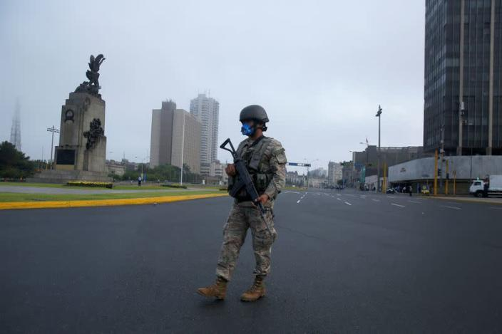 A soldier keeps watch after Peru's government deployed military personnel to block major roads, as the country rolled out a 15-day state of emergency to slow the spread of coronavirus disease (COVID-19), in Lima