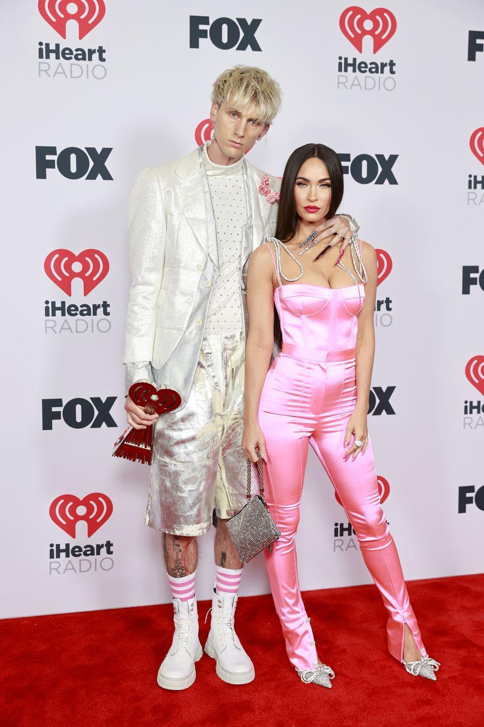 """<p>Fox wore a pink Mach & Mach jumpsuit with silver straps and matching heeled pumps to create this <a href=""""https://www.elle.com/uk/life-and-culture/a36565497/megan-fox-machine-gun-kelly-pink-outfits-iheartradio-music-awards-2021/"""" rel=""""nofollow noopener"""" target=""""_blank"""" data-ylk=""""slk:Barbie-inspired look"""" class=""""link rapid-noclick-resp"""">Barbie-inspired look</a>. </p>"""