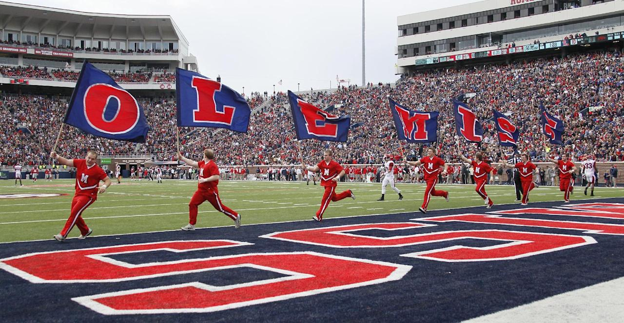 Mississippi cheerleaders carry flags spelling out the school's nickname after a touchdown during the first half of an NCAA college football game against Arkansas at Vaught-Hemingway Stadium in Oxford, Miss., on Saturday, Nov. 9, 2013. Mississippi won 34-24. (AP Photo/Rogelio V. Solis)