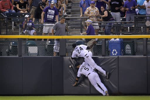 Colorado Rockies outfielder Dexter Fowler (24) collides with teammate Carlos Gonzalez as they chased a fly ball hit by Washington Nationals' Ryan Zimmerman for a double in the sixth inning of a baseball game on Wednesday, June 12, 2013, in Denver. (AP Photo/Joe Mahoney)