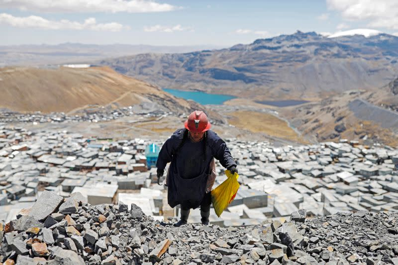 Eva Chura, 42, who is a pallaquera (a female gold picker) strikes rocks that were discarded from a mine in search of gold in the town of La Rinconada, in the Andes