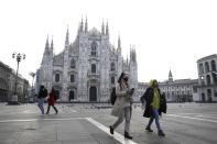 A woman wearing a sanitary mask walks past the Duomo gothic cathedral in Milan, Italy, Sunday, Feb. 23, 2020. A dozen Italian towns saw daily life disrupted after the deaths of two people infected with the virus from China and a pair of case clusters without direct links to the outbreak abroad. A rapid spike in infections prompted authorities in the northern Lombardy and Veneto regions to close schools, businesses and restaurants and to cancel sporting events and Masses. (AP Photo/Luca Bruno)