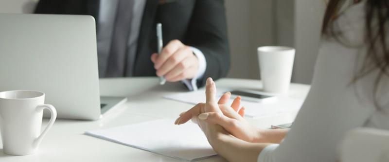 Close up of business people hands hold at an office desk, young man and woman are having a business talk. The woman feels stressed.