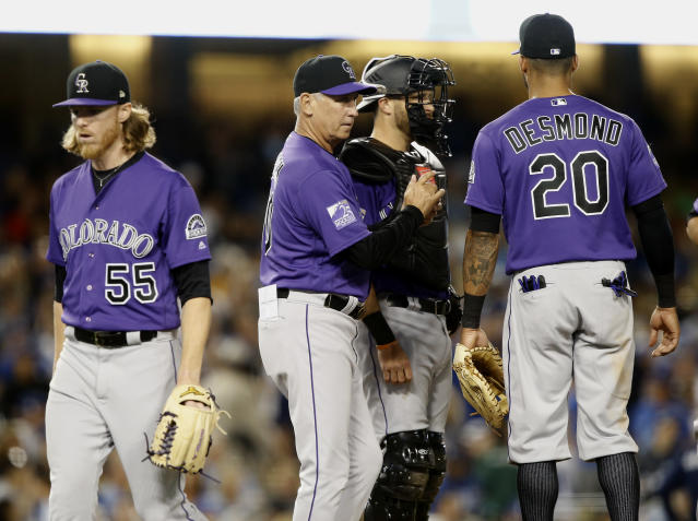 Colorado Rockies starting pitcher Jon Gray, left, walks off the mound after being pulled by manager Bud Black, second from left, with catcher Drew Butera and first baseman Ian Desmond, right, loking on during the third inning of a baseball game against the Los Angeles Dodgers in Los Angeles, Monday, Sept. 17, 2018. (AP Photo/Alex Gallardo)