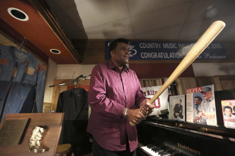 Country music legend Charley Pride looks at a bat among other items he is donating to the Smithsonian during an interview at his recording studio in Dallas, Texas, Monday, Sept. 24, 2012. The Smithsonian has selected Pride to be part of the new National Museum of African American History and Culture opening in 2015 with Pride giving the museum items from his life. (AP Photo/LM Otero)