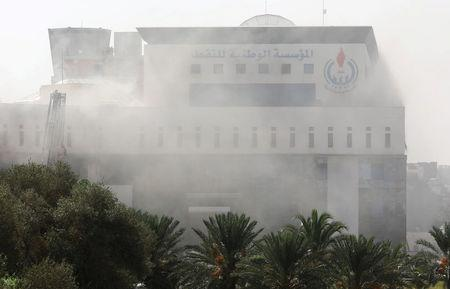 Smoke rises form the headquarters of Libyan state oil firm National Oil Corporation (NOC) after three masked persons attacked it in Tripoli