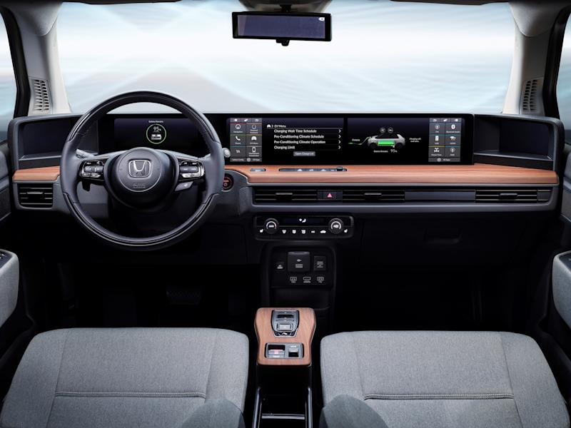A view of the front seats and dashboard of the Honda E Prototype, showing several touchscreens, reddish wood trim, and typical Honda cloth seats and steering wheel.