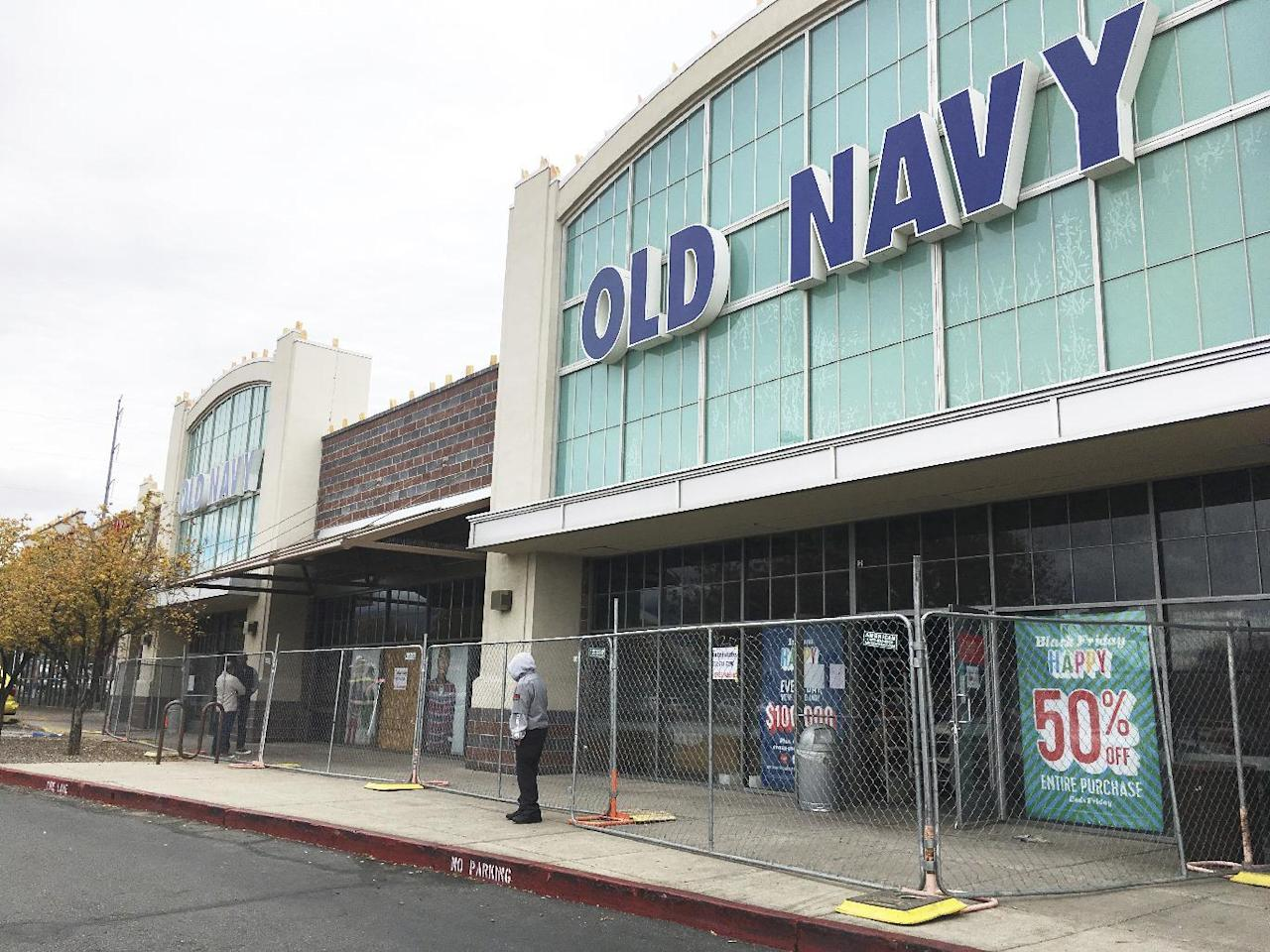 Workers clean up an Old Navy store in Albuquerque, N.M. on Monday, Nov. 28, 2016, two days after authorities say an explosive device damaged the store. Federal authorities charged a man on Monday with using an explosive device to damage the store, where a string of local, overnight fires and instances of vandalism during the busiest shopping weekend of the year also damaged three Starbucks shops, a Barnes & Noble and other establishments in New Mexico's largest city. (AP Photo/Russell Contreras)