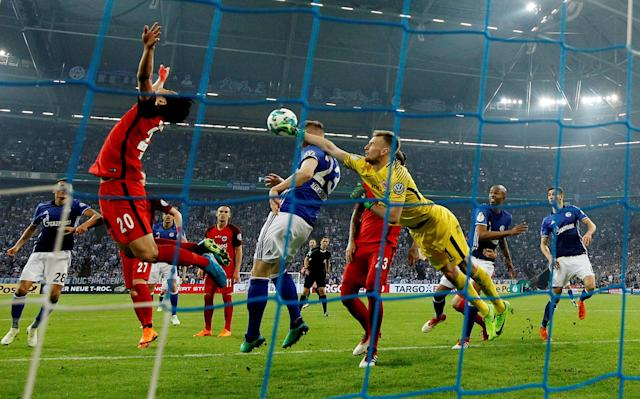 Soccer Football - DFB Cup - Schalke 04 vs Eintracht Frankfurt - Veltins-Arena, Gelsenkirchen, Germany - April 18, 2018 Eintracht Frankfurt's Lukas Hradecky in action with Schalke's Cedric Teuchert REUTERS/Leon Kuegeler DFB RULES PROHIBIT USE IN MMS SERVICES VIA HANDHELD DEVICES UNTIL TWO HOURS AFTER A MATCH AND ANY USAGE ON INTERNET OR ONLINE MEDIA SIMULATING VIDEO FOOTAGE DURING THE MATCH.