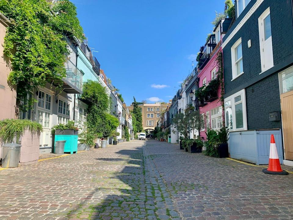 A straight shot of St. Lukes Mews with the famous pink house from Love Actually on the right and other colorful homes beside it.