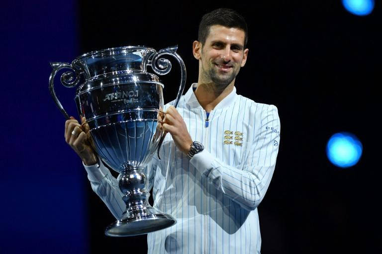 Novak Djokovic poses with the year-end No. 1 trophy