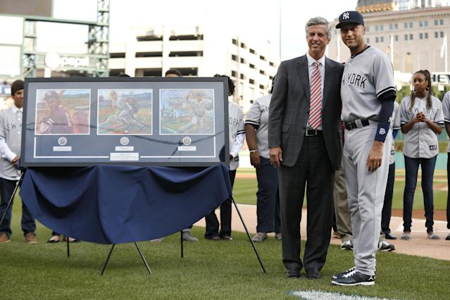 Detroit Tigers general manager Dave Dombrowski stands with New York Yankees shortstop Derek Jeter in a special on-field ceremony before a baseball game in Detroit Wednesday, Aug. 27, 2014. (AP Photo/Paul Sancya)