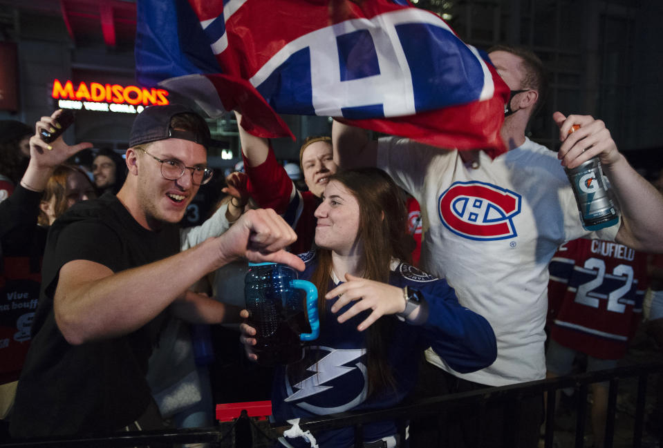 A Tampa Bay Lightning fan and a Montreal Canadiens fan react while watching coverage of the end of Game 5 of the NHL hockey Stanley Cup Finals, outside the Bell Centre in Montreal on Wednesday, July 7, 2021. (Ryan Remiorz/The Canadian Press via AP)