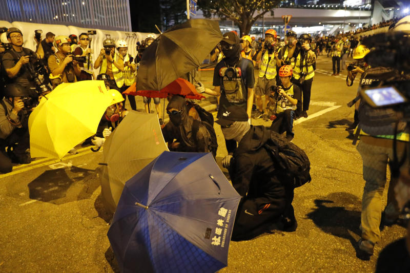 Black-clad protesters wearing goggles and masks hold umbrellas and stand outside government office in Hong Kong, Saturday, Sept. 28, 2019. Thousands of people gathered Saturday for a rally in downtown Hong Kong, belting out songs, speeches and slogans to mark the fifth anniversary of the start of the 2014 Umbrella protest movement that called for democratic reforms in the semiautonomous Chinese territory. (AP Photo/Vincent Thian)