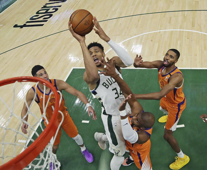 Milwaukee Bucks' Giannis Antetokounmpo (34) shoots over Phoenix Suns' Devin Booker, from left to right, Chris Paul and Mikal Bridges during Game 4 of basketball's NBA Finals, Wednesday, July 14, 2021, in Milwaukee. (Jonathan Daniel/Pool Photo via AP)