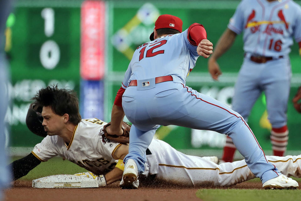 St. Louis Cardinals shortstop Paul DeJong (12) holds a tag on Pittsburgh Pirates' Bryan Reynolds who was out trying to stretch a single during the first inning of a baseball game in Pittsburgh, Saturday, Sept. 7, 2019. (AP Photo/Gene J. Puskar)