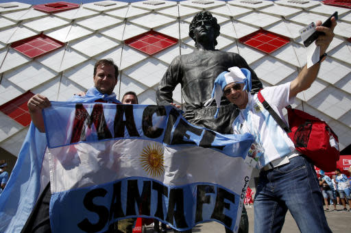 Argentine fans pose for a photo next to the stature of Russian player Fedor Cherenkov ahead of the group D match between Argentina and Iceland at the 2018 soccer World Cup in the Spartak Stadium in Moscow, Russia, Saturday, June 16, 2018. (AP Photo/Rebecca Blackwell)