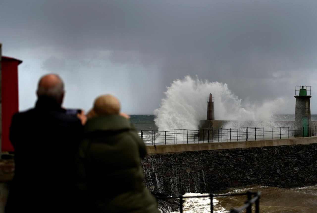 People take pictures as huge waves crash on the Viavelez seafront in the northern Spanish region of Asturias, Spain, December 11, 2017. REUTERS/Eloy Alonso     TPX IMAGES OF THE DAY