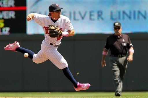 Minnesota Twins shortstop Brian Dozier, left, misses the throw to first base on a Toronto Blue Jays Rajai Davis hit during the third inning of a baseball game on Sunday, May 13, 2012, in Minneapolis. Dozier was given an error on the play. (AP Photo/Genevieve Ross)