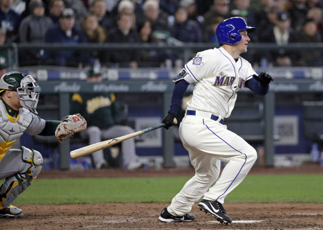 Seattle Mariners' Kyle Seager, right, grounds out to end a baseball game as Oakland Athletics catcher Bruce Maxwell looks on in the ninth inning Sunday, April 15, 2018, in Seattle. (AP Photo/Elaine Thompson)