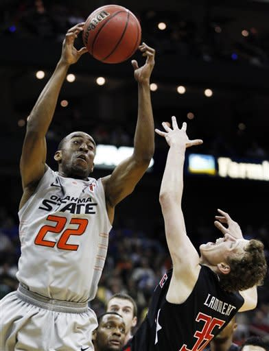 Oklahoma State guard Markel Brown (22) rebounds over Texas Tech forward Clark Lammert (35) during the first half of an NCAA college basketball game in the Big 12 Conference tournament, Wednesday, March 7, 2012, in Kansas City, Mo. (AP Photo/Orlin Wagner)