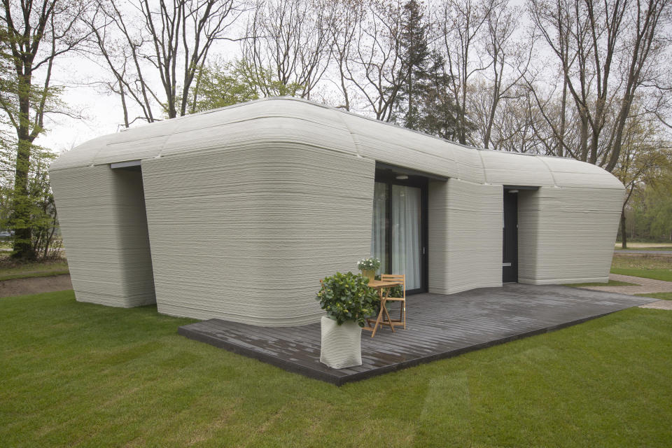 Exterior view of the 3D-printed 94-square meters (1,011-square feet) two-bedroom bungalow resembling a boulder with windows in Eindhoven, Netherlands, Friday, April 30, 2021. The fluid, curving lines of its gray walls look natural. But they are actually at the cutting edge of housing construction in the Netherlands and around the world. They were 3D printed at a nearby factory. (AP Photo/Peter Dejong)