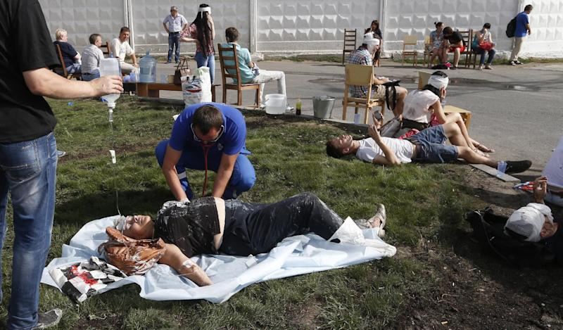 Paramedics treat passengers injured as several subway cars derailed in Moscow, on July 15, 2014