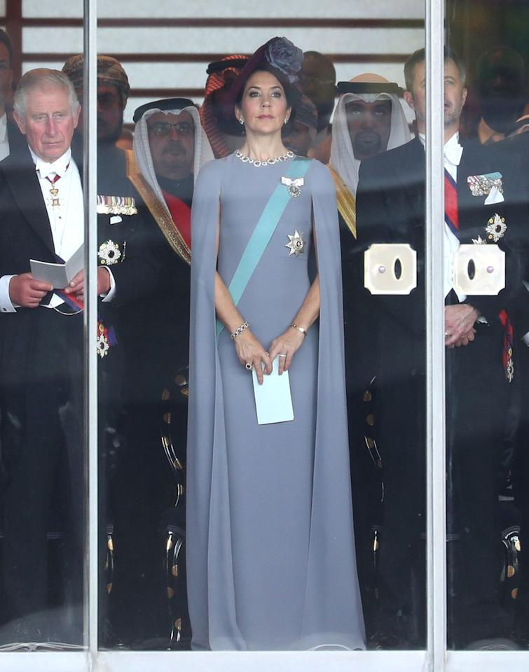 <p>During a trip to Japan, Princess Mary chose a blue-grey gown with an attached cape. She complemented the look with a turquoise sash, ceremonial brooches, and a purple hat with a large blue flower.</p>