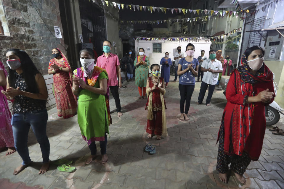 FILE - In this Wednesday, Oct. 21, 2020, file photo, Indians, wearing face mask and maintaining physical distance, participate in religious rituals during Navratri festival celebrations in Ahmedabad, India. Weeks after India fully opened up from a harsh lockdown and began to modestly turn a corner by cutting new infections by near half, a Hindu festival season is raising fears that the disease could spoil the hard-won gains. Health experts worry the festivals can set off a whole new cascade of infections, further testing and straining India's battered health care system. (AP Photo/Ajit Solanki, File)